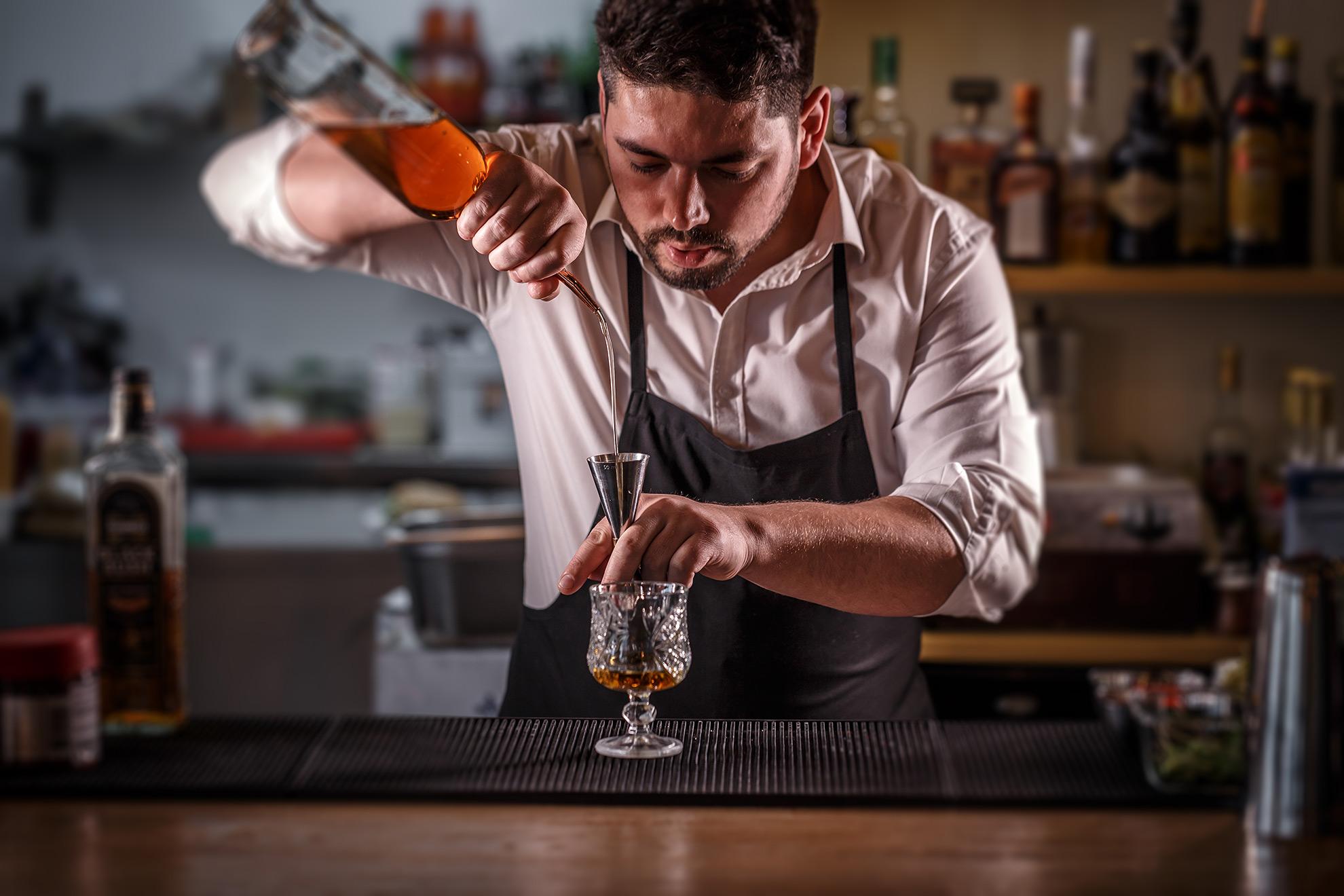 Barman nalewający alkohol za pomocą jiggera