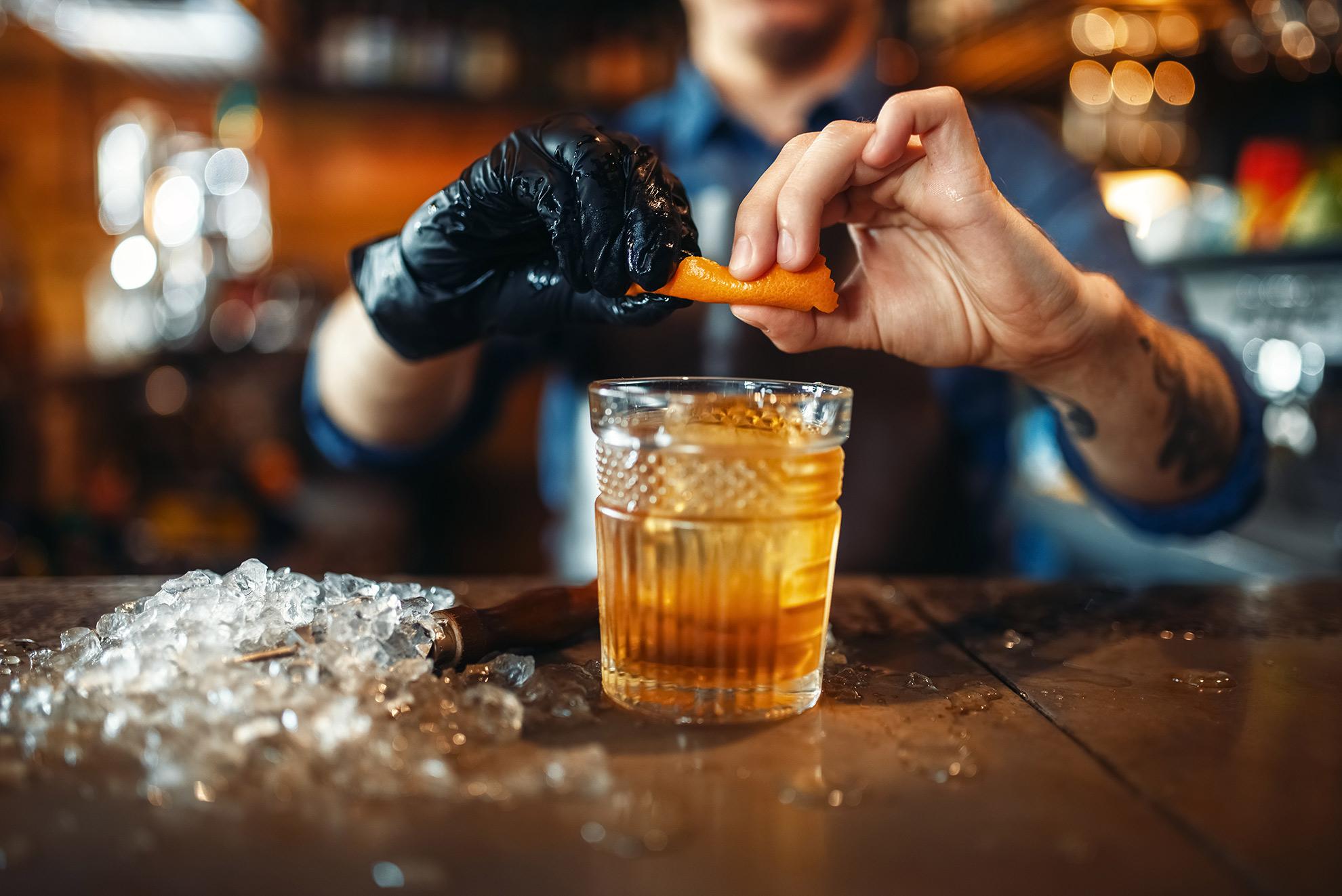 Barman wyciskający skórkę pomarańczy, ilustracja do artykułu o old fashioned
